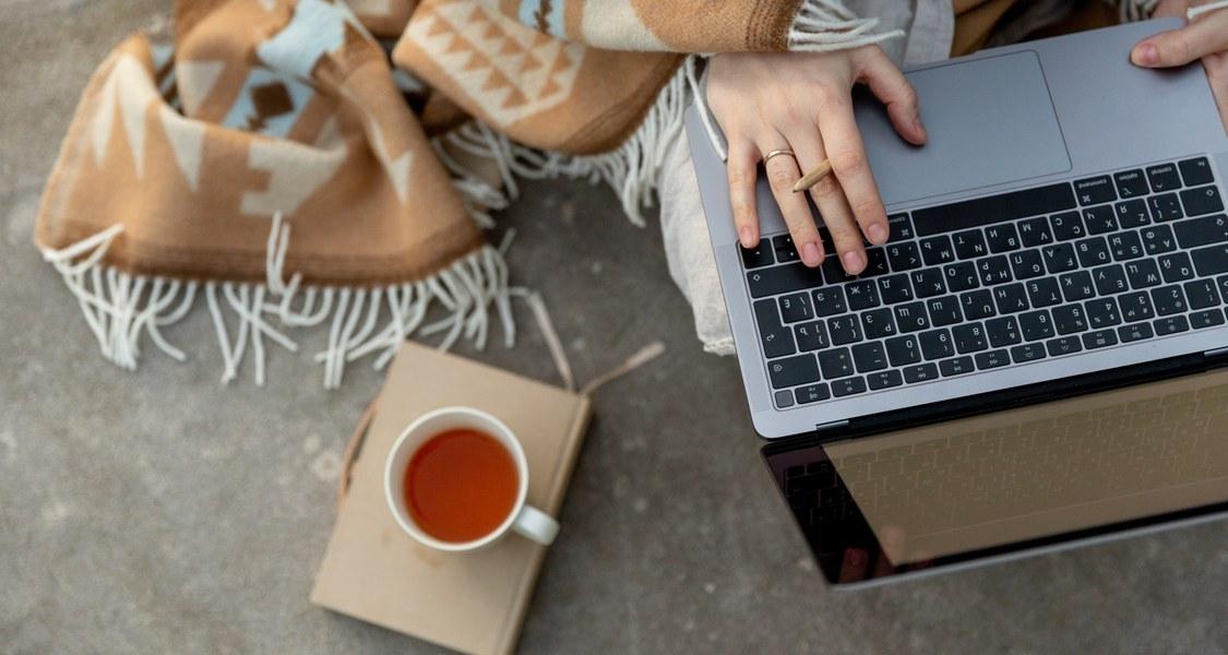 Person mit Laptop und heißem Tee