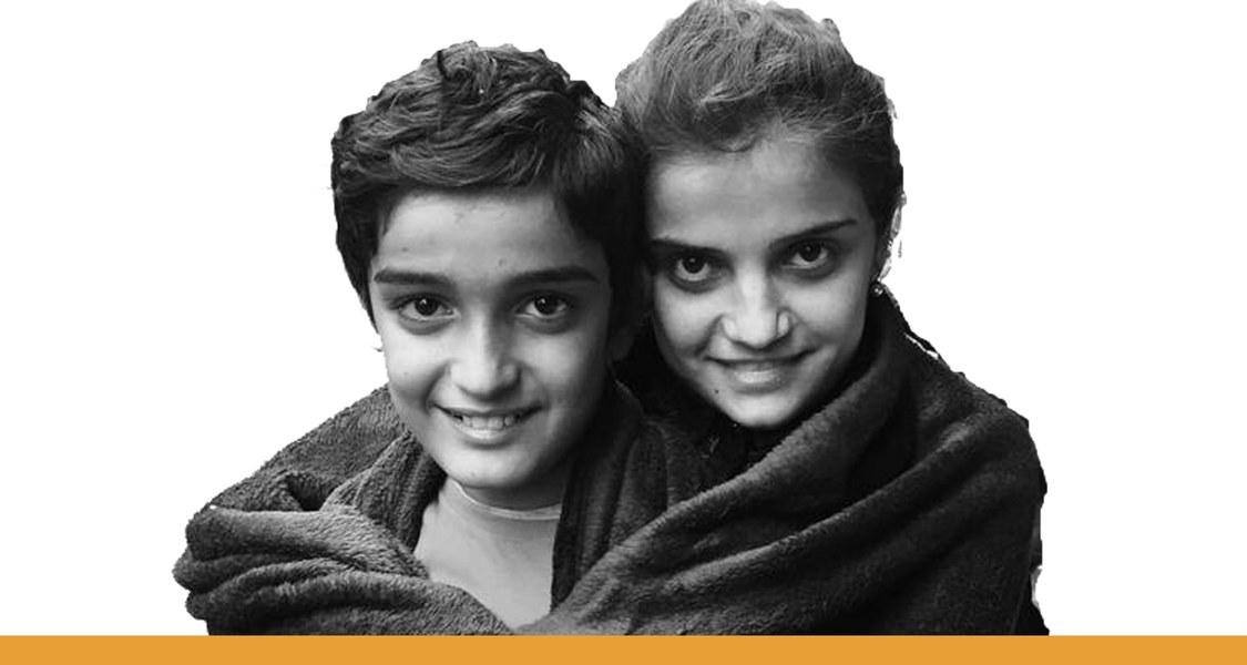 Junge und Mädchen, in eine Decke gehüllt und sich einander umarmend, lächelnd mit Blick auf den Betrachter