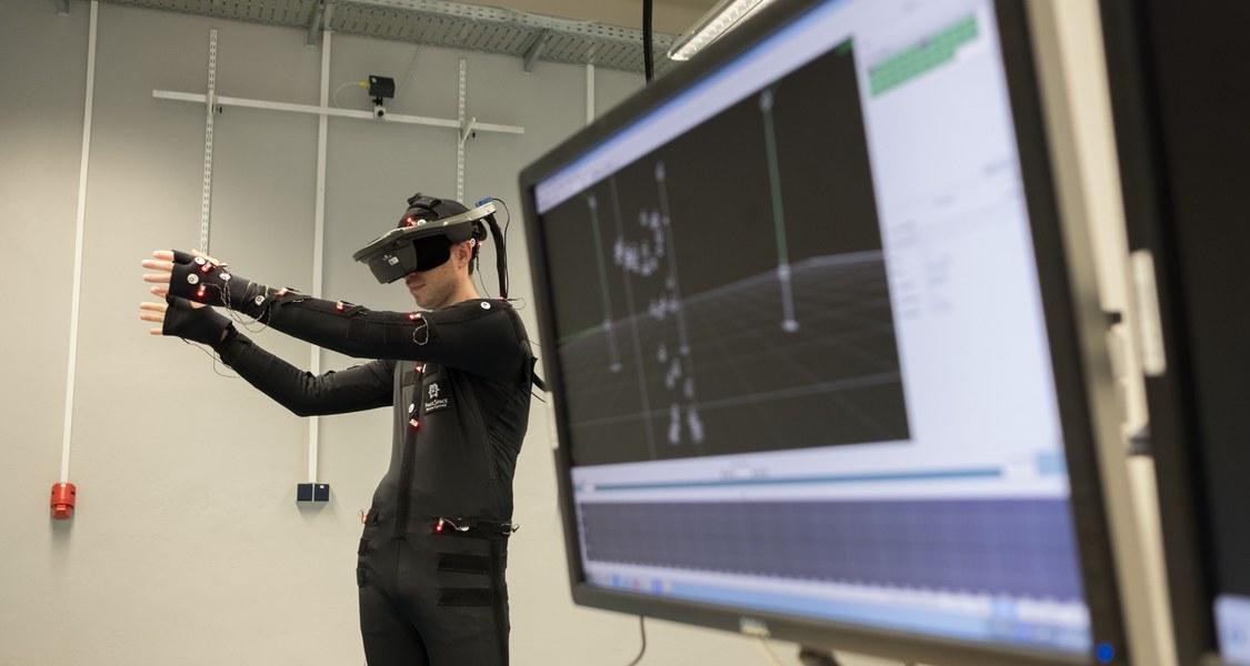 Eine Person in einem Motion Capture Anzug und Virtual Reality Brille greift nach virtuellen Boxen. Im Vordergrund sieht man einen Monitor mit Motion Capture Software.