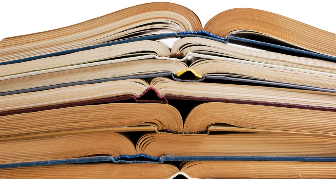 Stapel aus aufgeklappten Büchern