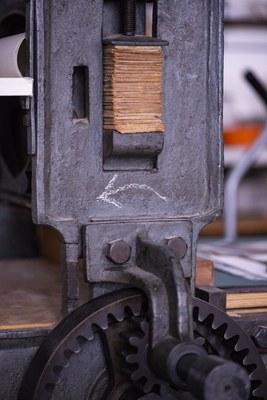 Manuelle Lithographiepresse, Kurbelrichtung wird durch einen Pfeil angezeigt. Der Pfeil zeigt nach links.