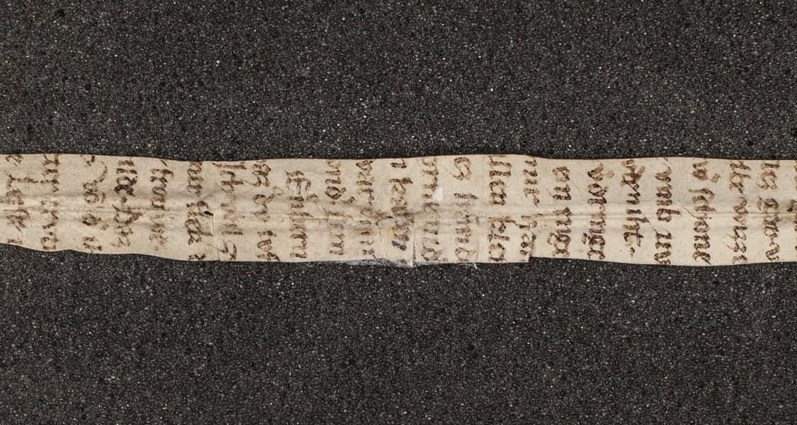 """Ein Streifen Pergament, der einen Textausschnitt des """"Rosendorn""""-Gedichtes enthält"""