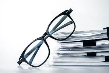 Ein Stapel Papier und eine Brille liegen auf einem Tisch.