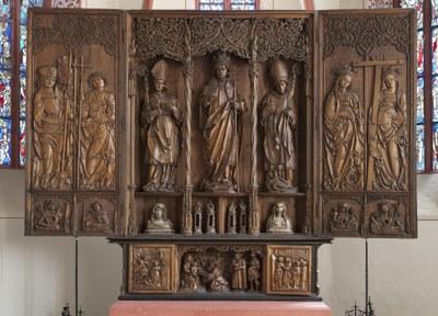 Holzsichtiges Triptychon mit Heiligendarstellungen.