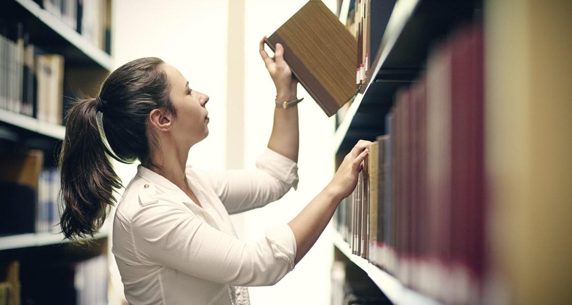 Studentin entnimmt Buch aus einem Regal in einer Bibliothek