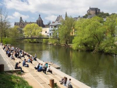 Studierende sitzen auf der Lahntreppe; Blick auf Schlossberg.