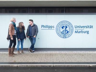 Drei Studierende neben dem Logo der Uni Marburg am Hauptgebäude in der Biegenstraße.jpg