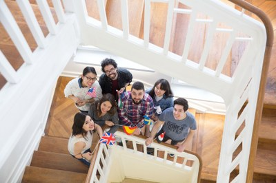 Austauschstudierende mit verschiedenen kleinen Landesflaggen im Treppenhaus des International Office in der Deutschhausstraße