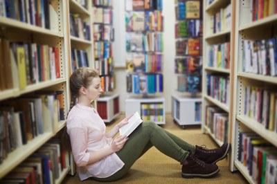 Eine Studierende liest ein Buch auf dem Boden einer Bibliothek