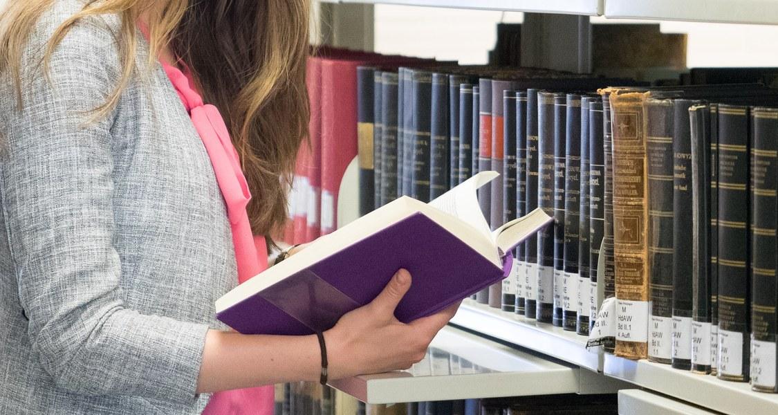 Studierende liest ein Buch vor einem Bibliotheksregal.