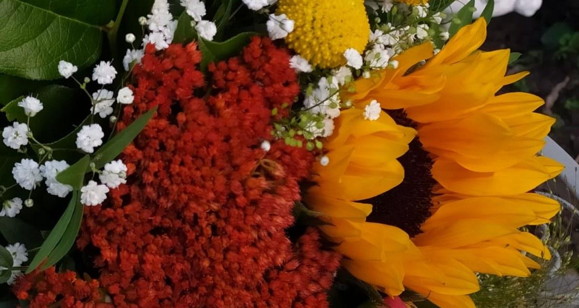 großer Blumenstrauß mit Sonnenblume in der Mitte und zwei Engeln links und rechts darüber, die auf den Strauß blicken