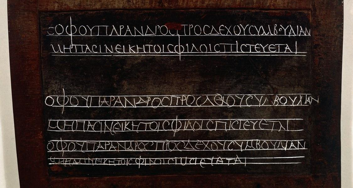 Wachstafel zeigt Übungen eines griechischen Schülers. Die Tafel enthält zwei Zeilen, oben ordentlich als Vorlage geschrieben und dann zweimal kopiert.