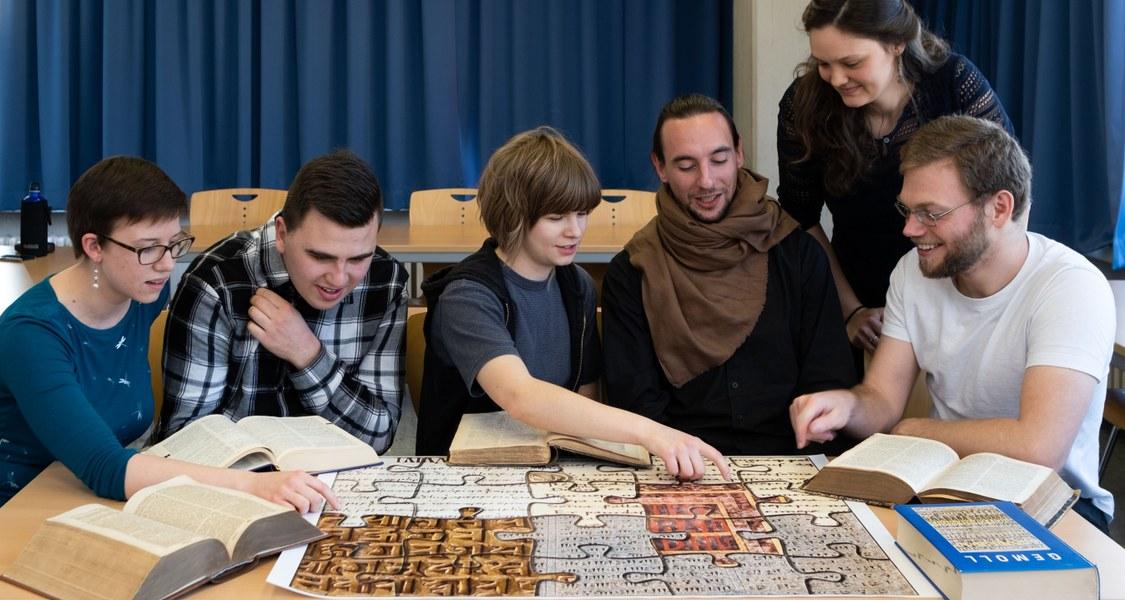 Studierende erkunden klassische Sprachen mit Sprachenpuzzle und Wörterbüchern