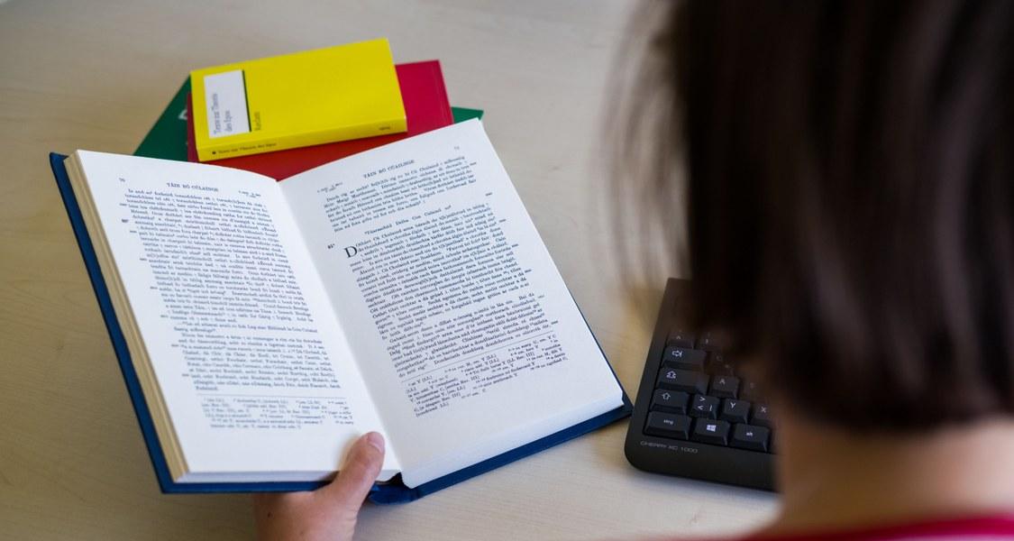 Blick über die Schulter eines Studierenden in ein offenes Buch