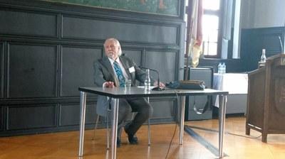 Henry Beissel sitzt an einem Tisch im historischen Rathaussaal von Marburg