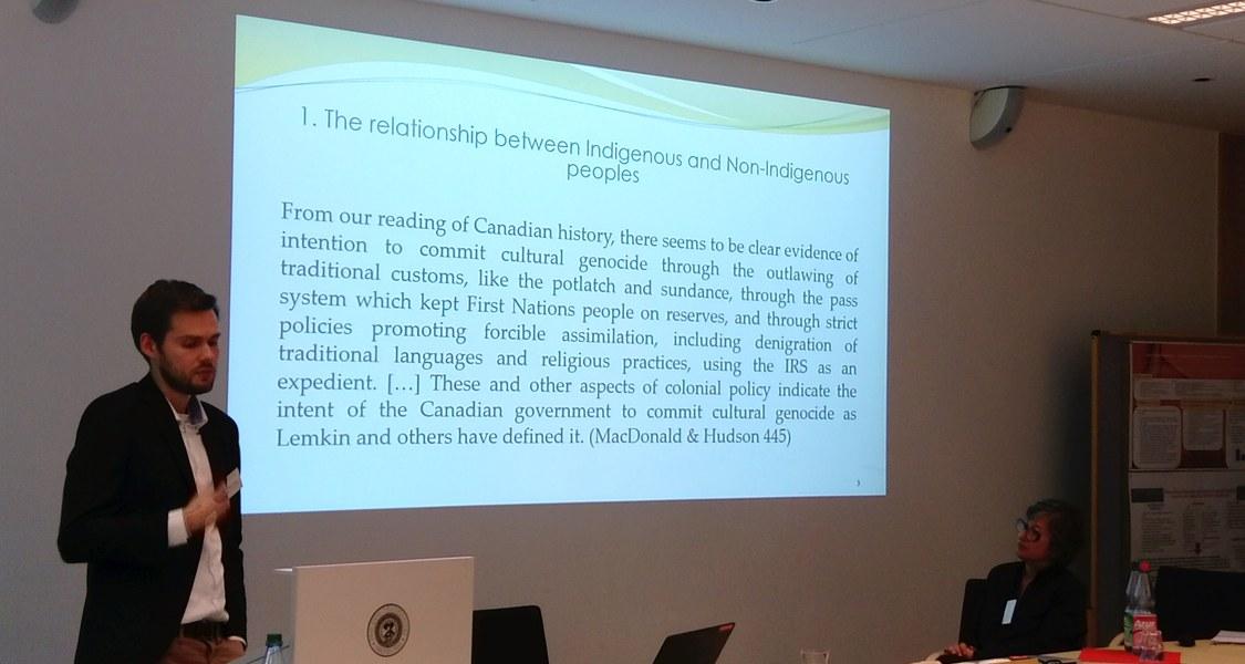 Ein junger Mann erklärt etwas, hinter ihm eine Powerpoint-Folie zu indigenen Menschen Kanadas an der Wand