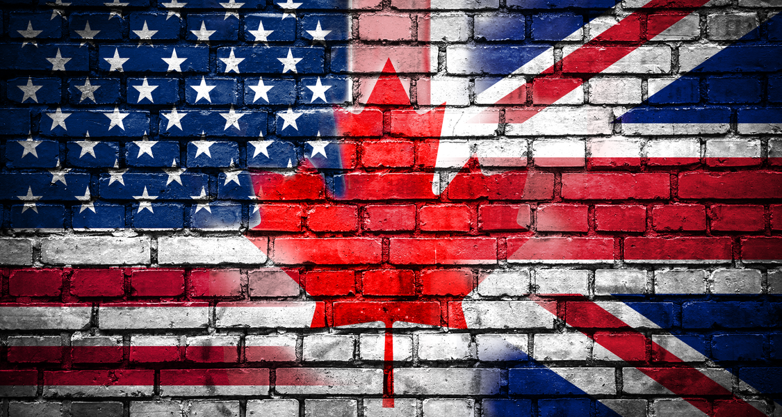 Flags for USA, GB and Canada on brick wall background, blended into one another