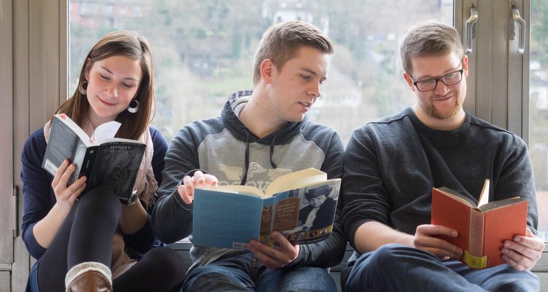 Studierende lesen Bücher vor einem Fenster der Philosophischen Fakultät