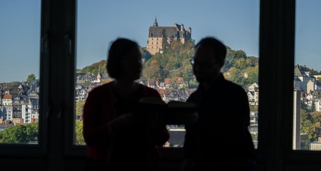 Zwei nicht erkennbare Personen vor einem Bürofenster mit Blick auf das Marburger Schloss im Fokus