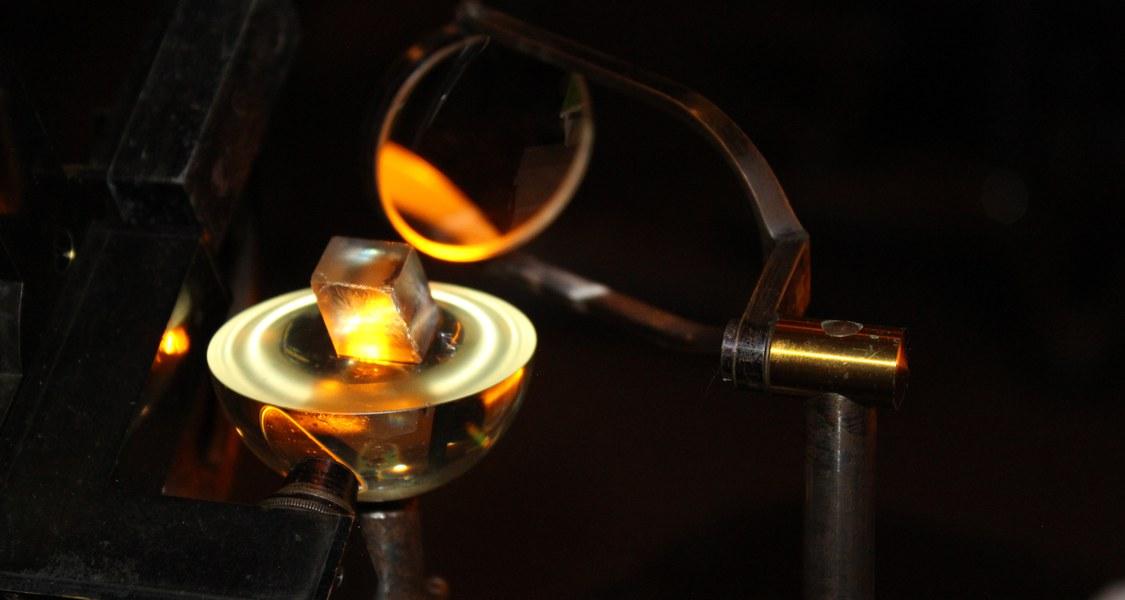 Mit dem Abbe'schen Kristallrefraktometer wurden zu Beginn des 20. Jh. die optischen Eigenschaften von Kristallen untersucht.  Vor allem Effekte wie die Doppelbrechung standen im Fokus. Das Bild zeigt die Vermessung eines Kalkspatkristalls.