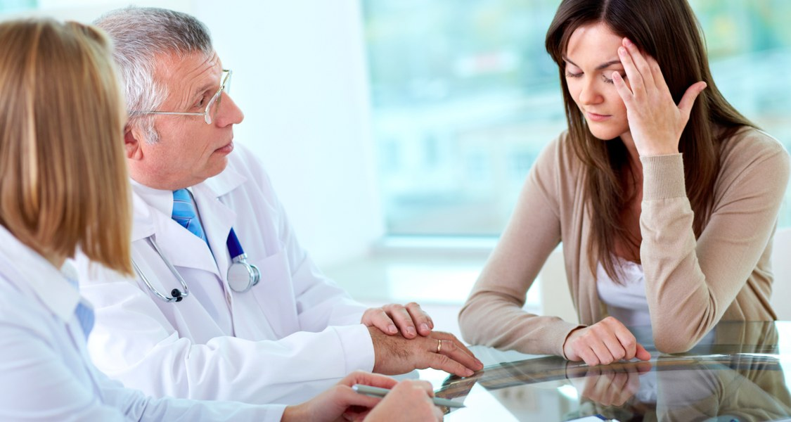 Portrait of two practitioners consulting patient