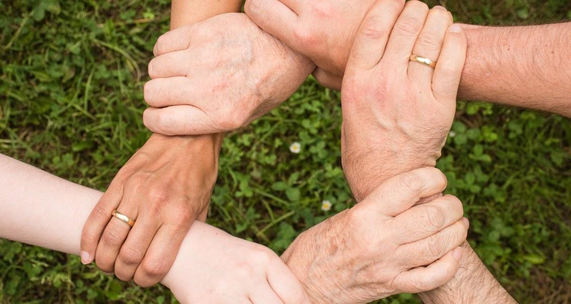 Hände verschiedener Personen greifen ineinander