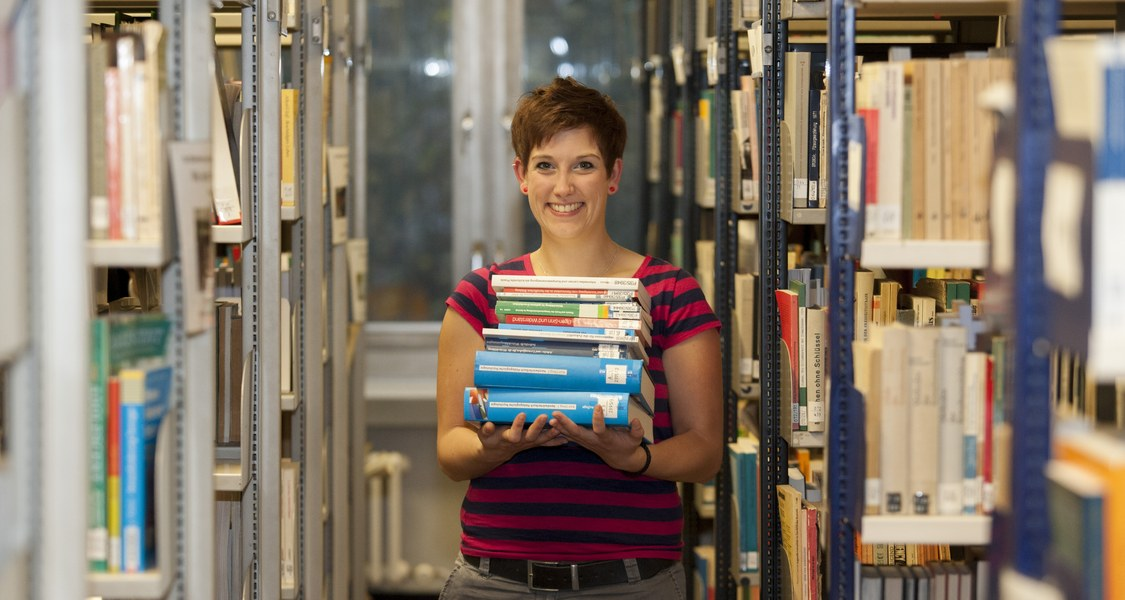 Studentin mit Büchern in Bibliothek