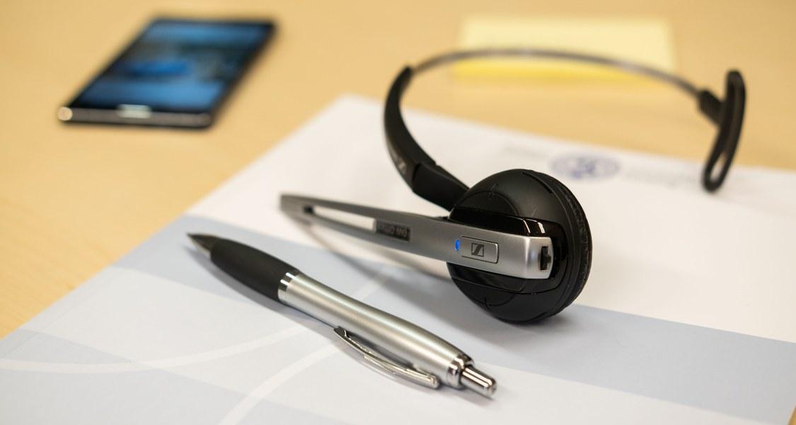 Ein Schreibtisch mit einem Headset, einer Mappe und einem Smartphone