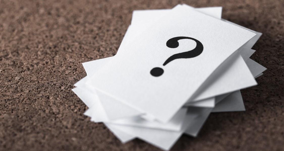 Ein Stapel Papier mit Fragezeichen darauf.
