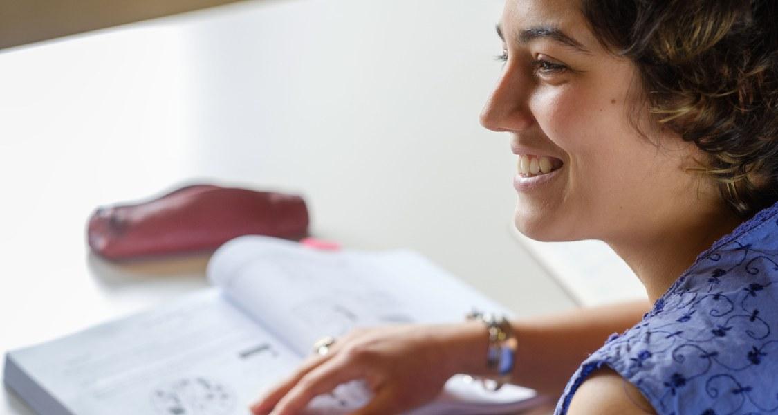 Studentin schaut von Buch auf und lächelt.