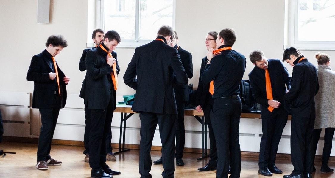 Unichoristen, die ihre Krawatte anziehen
