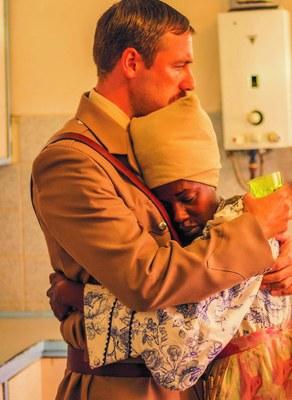 Ein Weißer Mann und eine Schwarze Frau halten sich eng umschlungen