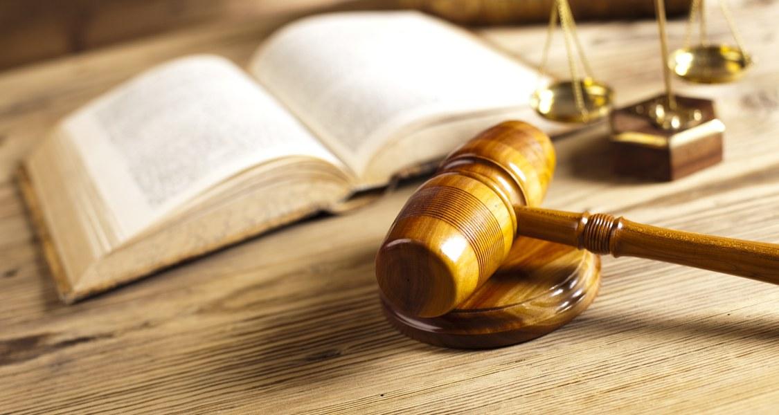 Buch, Waage und Richterhammer symbolisieren Utensilien des Gerichtsalltags