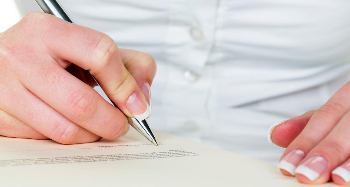 Person, die mit einem Kugelschreiber auf einem Blatt schreibt.