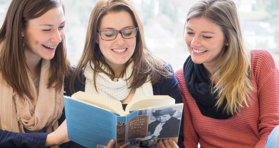 Drei Frauen lesen sitzend ein Buch