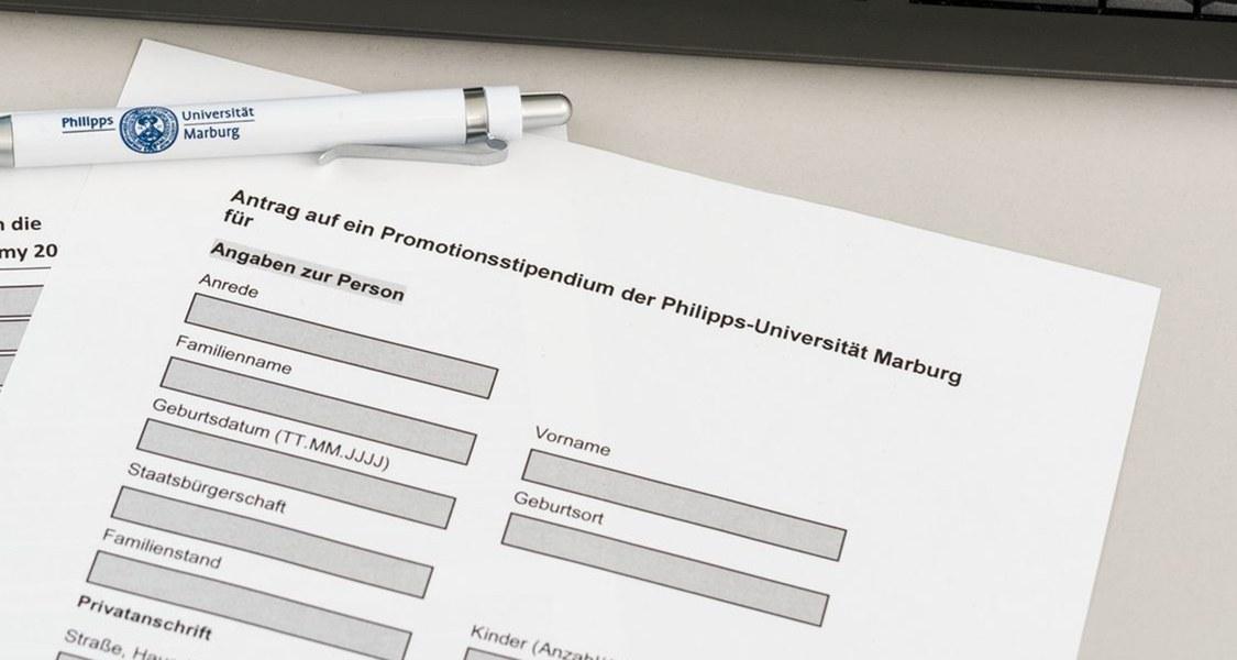 Formular eines Promotionsstipendiums und ein Kugelschreiber