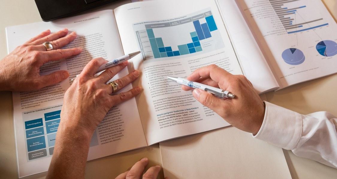 Dokument liegt auf einem Tisch, vier Hände liegen auf Dokument, zwei davon halten Kugelschreiber