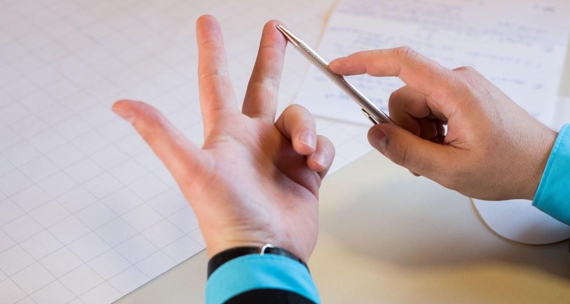 Eine Hand über einem Tisch zählt etwas an den Fingern ab