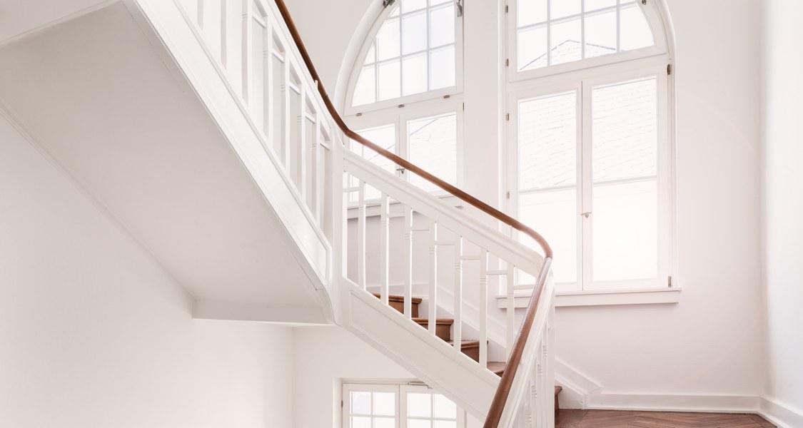 Weißer Treppenaufgang mit Fenster