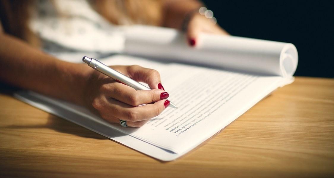 Nahaufnahme einer Hand, die mit einem Stift einen Text korrigiert