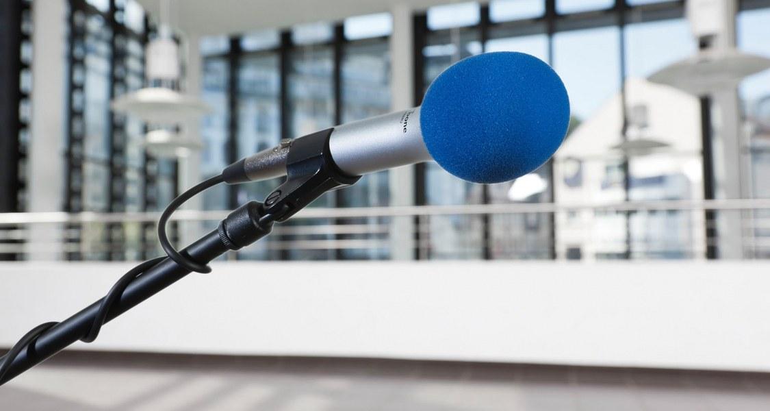 Mikrofon liegt auf einem Tisch mit ein paar Stühlen im Hintergrund