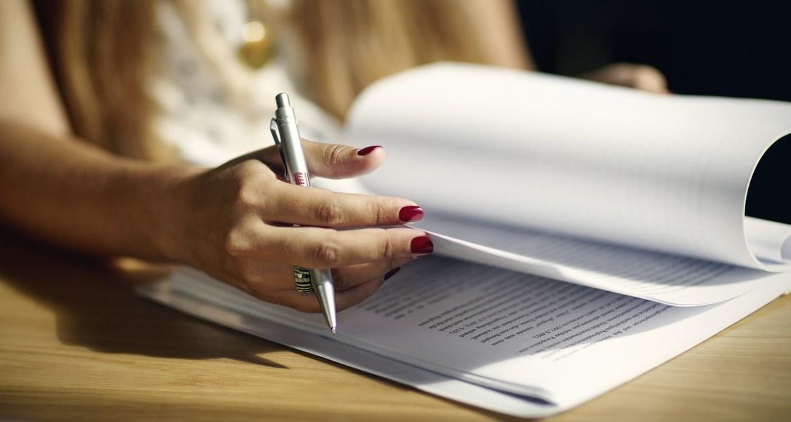 aufgeblättertes Heft, Hand mit Schreibstift