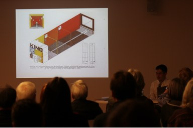 Das Publikum blickt auf die Leinwand. Sebastian Helm gibt Einblicke in die Hintergründe des Filmprojekts.