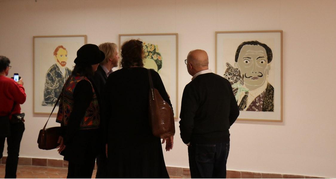 Im Anschluss an die Veranstaltung betrachten einige Personen gemeinsam mit der Künstlerin Perihan Arpacilar ihre Holzschnitte. Fünf Personen stehen mit dem Rücken zu uns.