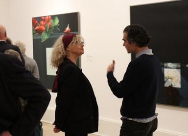 Zwei Personen unterhalten sich angeregt. Im Hintergrund sind mehrere Personen und die Kunstwerke von Rolf Gith zu sehen.