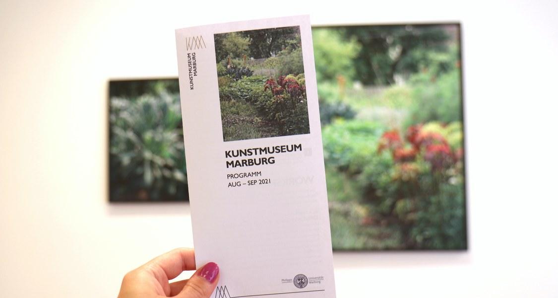 Zu sehen ist der Flyer des neuen Quartalsprogramms. Er wird in die Luft vor ein Kunstwerk von Franziska Klose gehalten.
