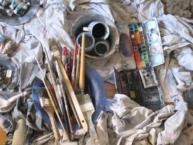 Zu sehen sind Tücher, Pinsel und Farben; Malutensilien der Künstlerin in vorwiegend Blautönen