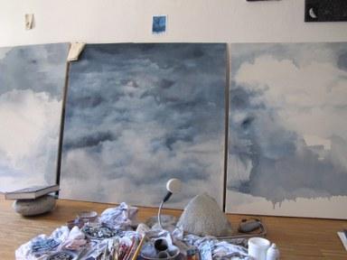 An der Stirnseite des Ateliers stehen auf dem Boden drei großformatige Gemälde. Sie zeigen Wolkenlandschaften in unterschiedlichen Abstraktionen. Die Leinwände auf der linken und rechten Seite weisen noch einige weiße Stellen auf.