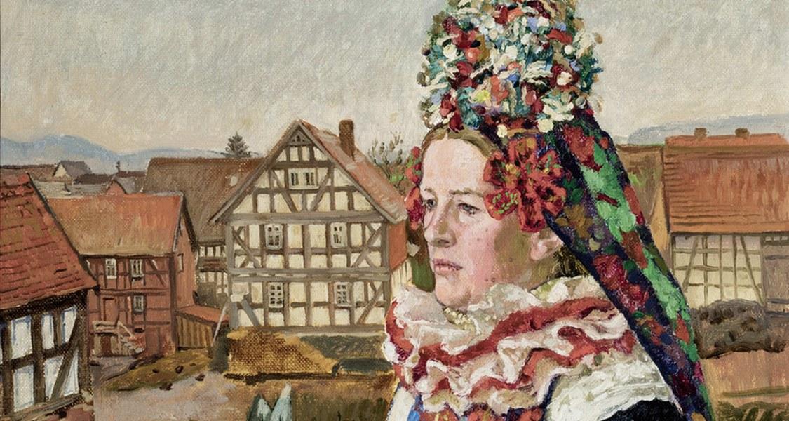 Frau in traditioneller Mardorfer Hochzeitstracht. Hinter der von Blumengewächsen umgebenen Braut zeigt sich eine Dorflandschaft.