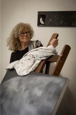 Doris Conrads hinter einer Staffelei mit Mondlandschaft